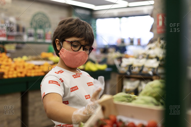 Boy taking vegetables in supermarket