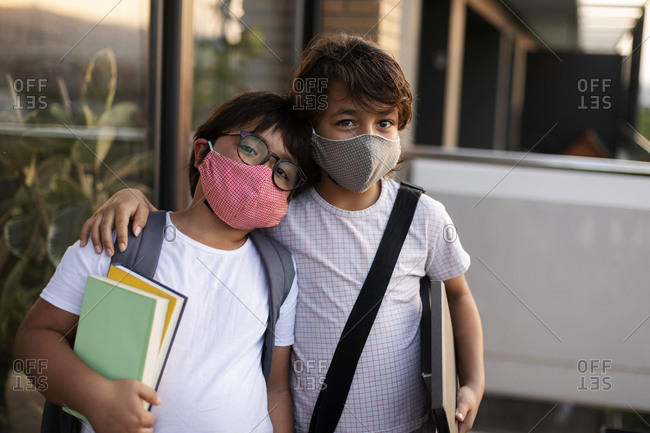 Siblings with books wearing masks outdoors