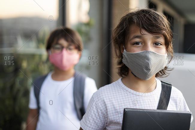 Siblings wearing cloth masks outdoors