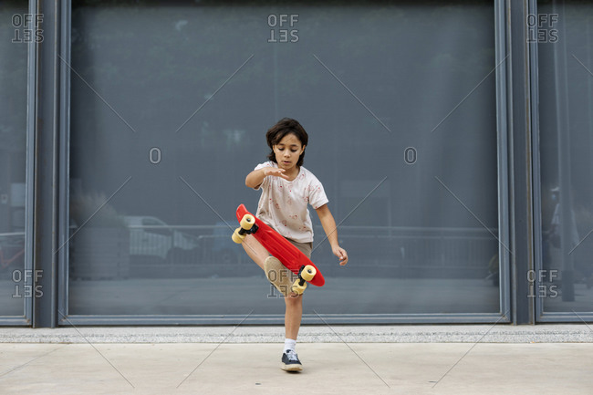 Boy practicing stunt with skateboard while standing on footpath against wall
