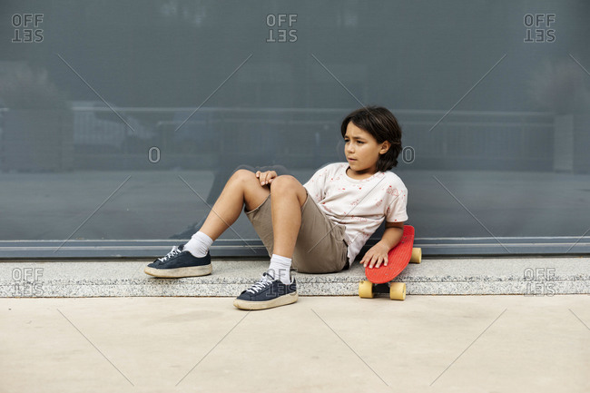 Thoughtful boy with skateboard relaxing on footpath against wall