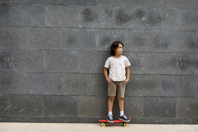 Thoughtful boy with hands in pockets standing on skateboard against wall