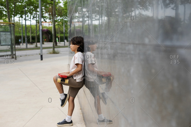 Boy holding skateboard looking away while standing by wall in park