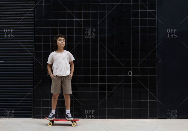 Boy with hands in pockets standing on skateboard against wall