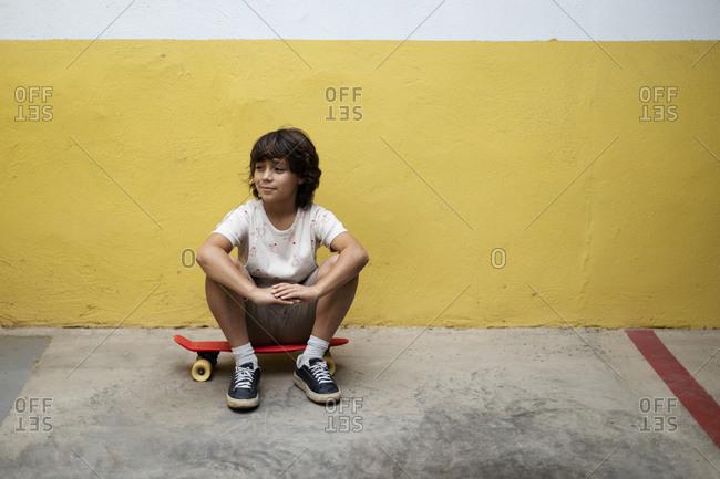 Thoughtful boy sitting on skateboard against wall