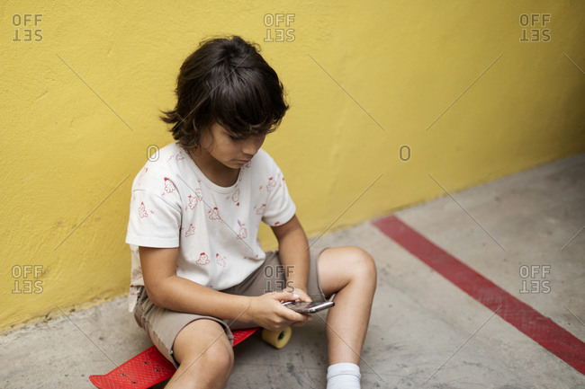 Boy using mobile phone while sitting on skateboard against wall
