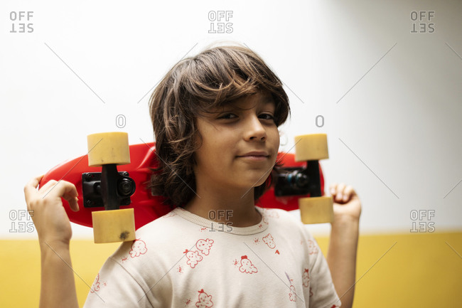 Close-up of boy holding skateboard while standing against wall