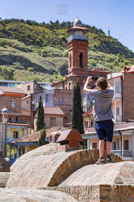Young man photographing Jumah Mosque and residential buildings in Tbilisi- Georgia