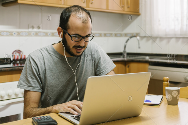 Man video conferencing on laptop while working at home