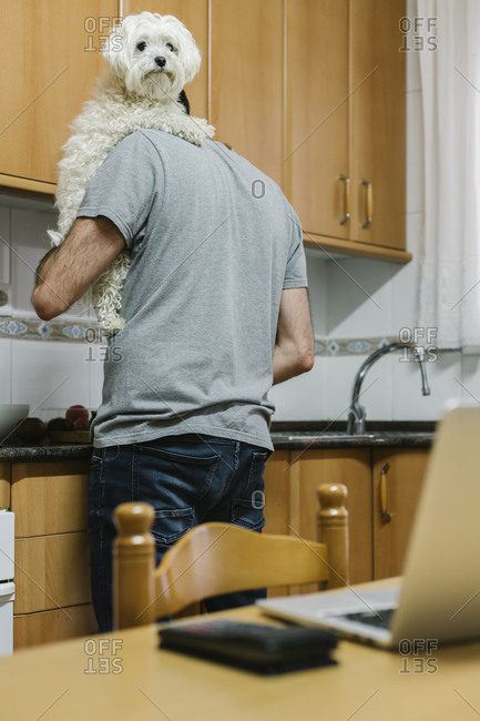 Man carrying dog while cooking in kitchen