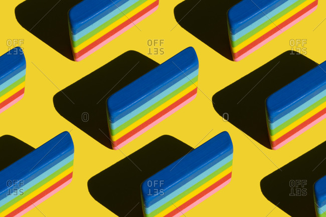 Pattern of rainbow colored erasers against yellow background