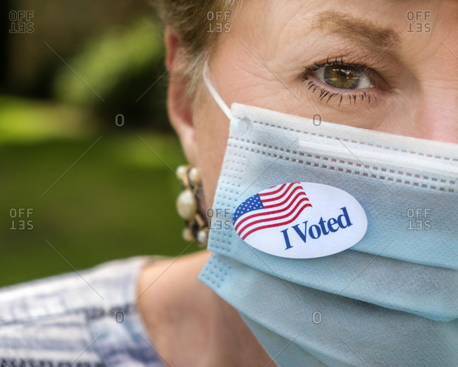 Close-up of woman in surgical mask and of I voted sticker