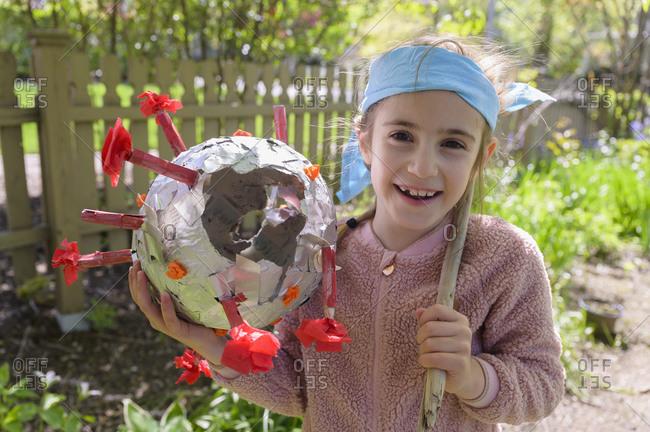 Smiling girl (6-7) holding coronavirus shaped pinata