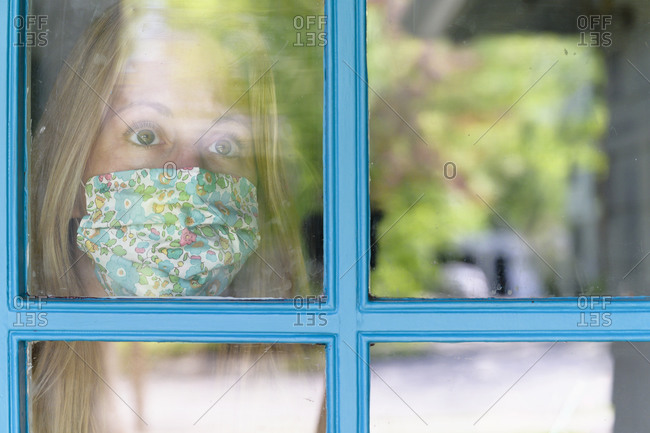 Woman in face mask looking through window