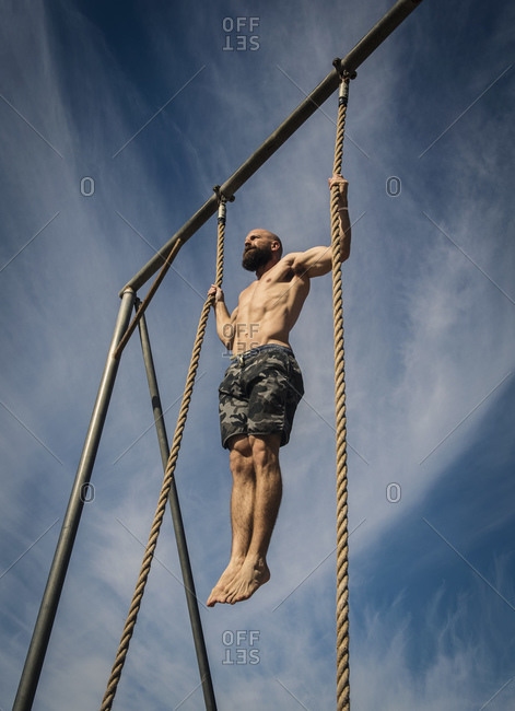 Bare-chested man exercising on rope