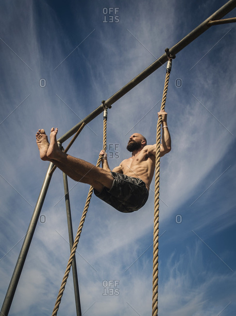 Bare-chested man exercising on rope, holding his legs up