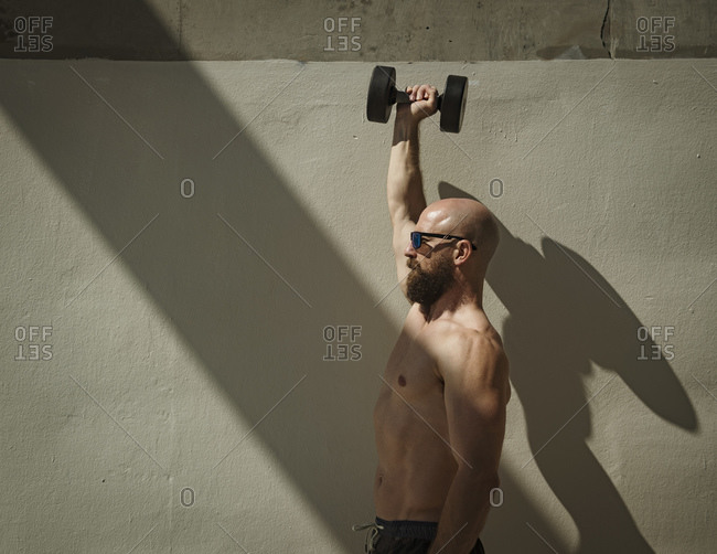 Man exercising with dumbbell in the shade