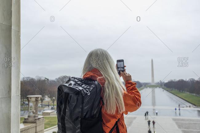 USA, Washington D.C., Tourist takes photo of Washington Monument across pond at National Mall using smartphone