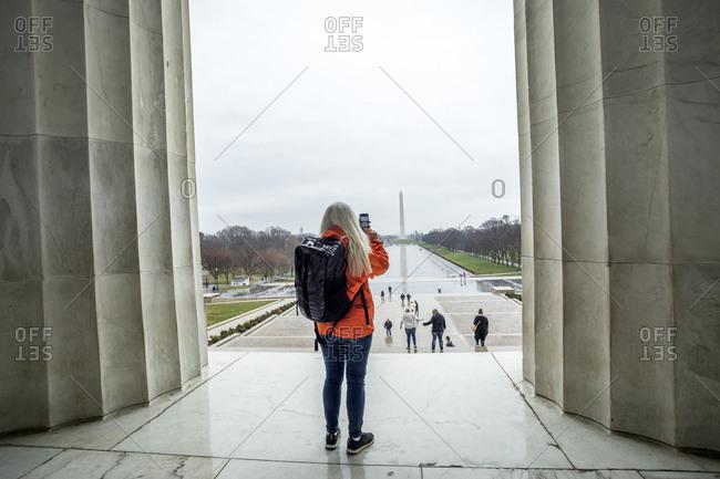 USA, Washington, Tourist takes photo of Washington Monument across pond at National Mall using smartphone
