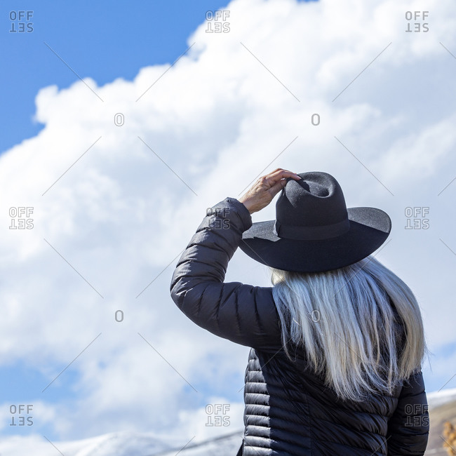 Portrait of senior woman wearing hat against blue sky and clouds