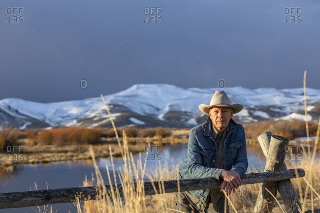 USA, Idaho, Sun Valley, Senior man in cowboy hat leaning against fence