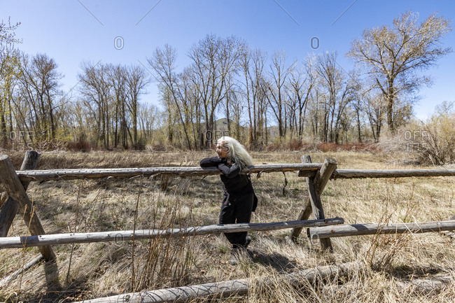 USA, Idaho, Bellevue, Senior woman relaxing on rustic rail fence