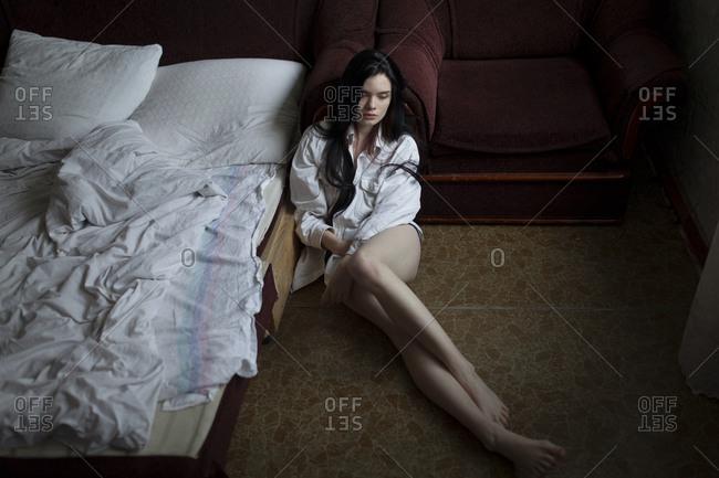 Semi-dress woman sitting on floor in bedroom