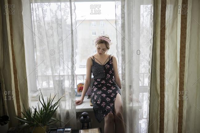 Woman sitting on window sill
