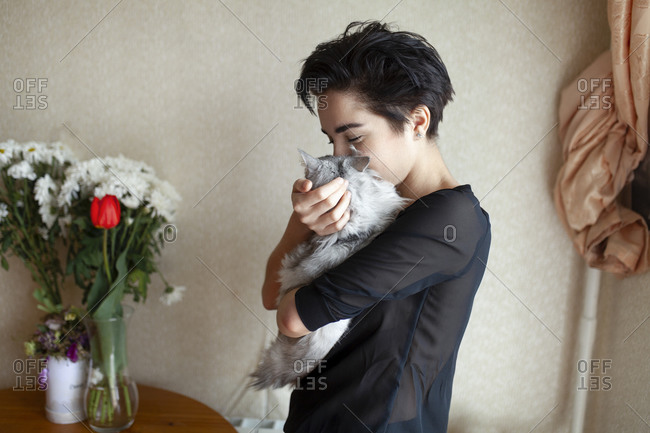 Woman cuddling cat at home