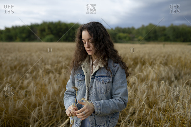 Russia, Omsk, Young woman standing in wheat field and holding wheat