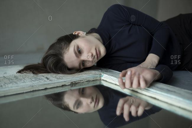 Teenage girl lying by mirror