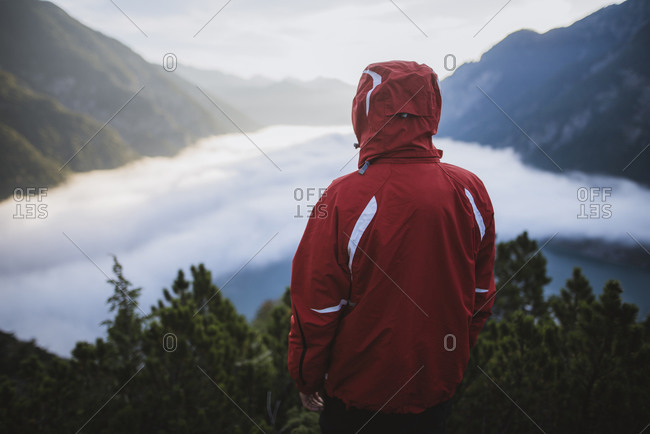 Austria, Plansee, Rear view of man in red jacket standing in Austrian Alps