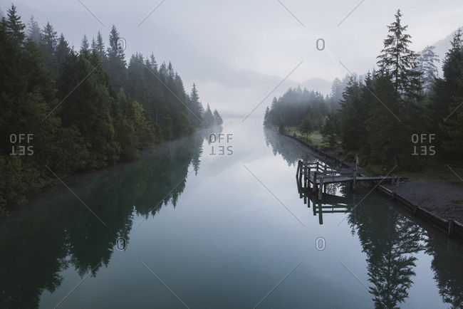Austria, Plansee, Lake Plansee and wooden pier in fog at Austrian Alps
