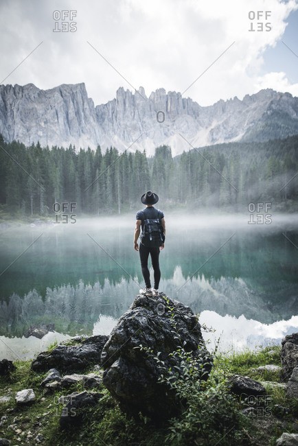 Italy, Carezza, Young man standing on rock at Lago di Carezza in Dolomite Alps at dawn