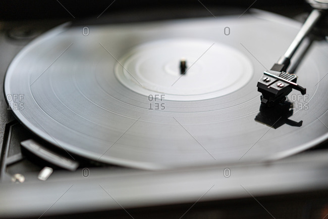 A black vinyl record is spinning on a vintage record player