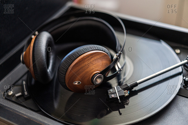 Vintage headphones made of wood are on a black vinyl in a record player