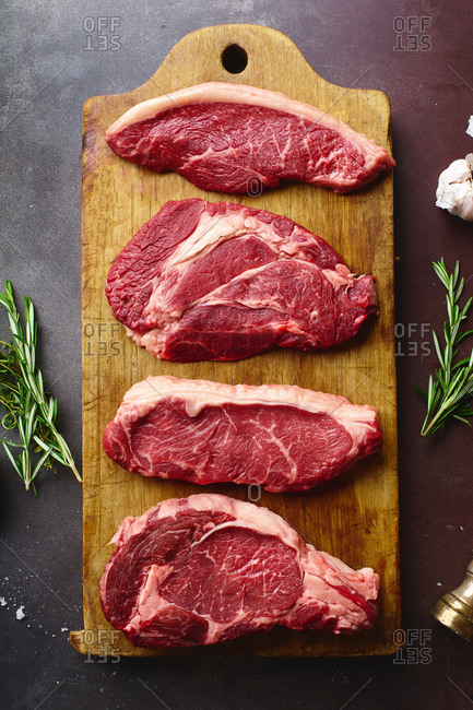 Top view of raw black angus prime beef steaks on wooden cutting board: rib eye, chuck roll, striploin and picanha.