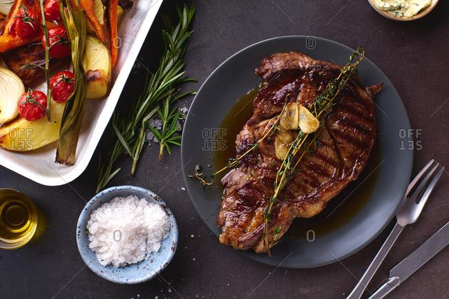 Cooked ribeye black angus prime beef steak with herbs, sea salt and grilled vegetables.