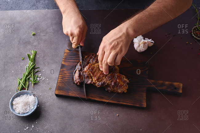Male hands cutting cooked until medium ribeye steak on wooden cutting board.