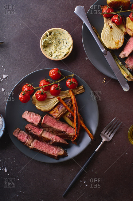 Cooked ribeye steak with roasted vegetables served with herb butter.