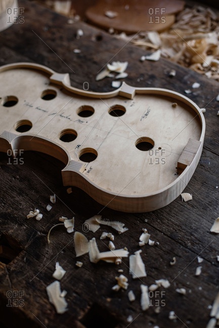 High angle of wooden soundboard with round holes and attached shells on workbench with sawdust in workshop