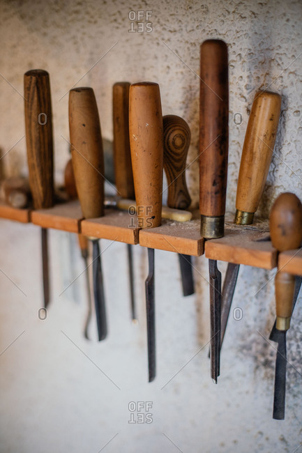 Set of assorted professional carpentry tools with wooden handles placed on shelf hanging on gray plastered wall in workshop