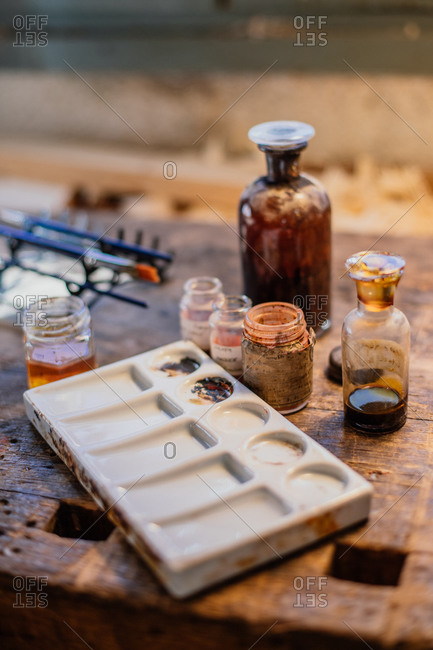Set of glass bottles and jars with varnish and special chemicals for carpentry work in composition with plastic palette on wooden workbench in workroom