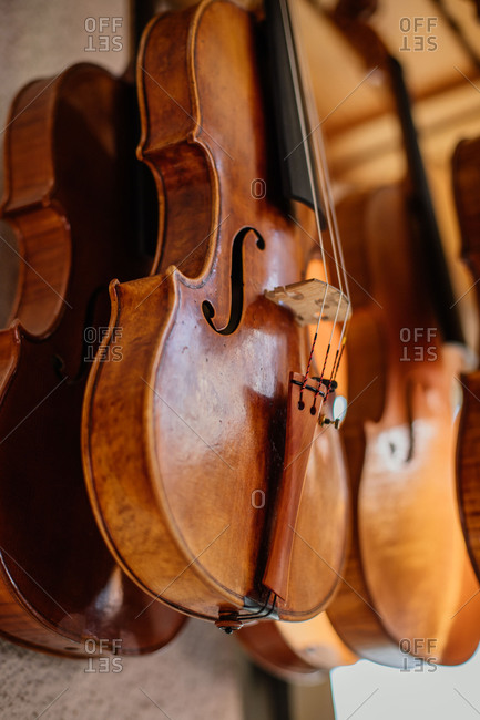 Collection of violins hanged at ceiling and drying after lacquering outdoors against blurred exterior of light modern workshop