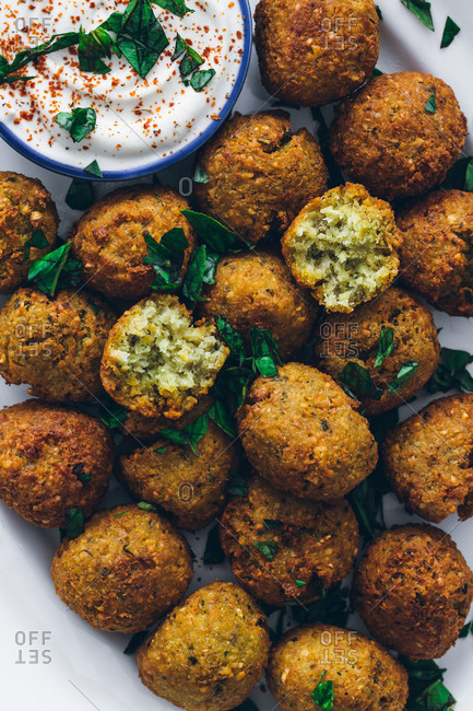 Top view of fried falafel made of legumes served with sour cream sauce on plate