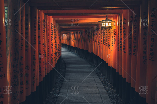 February 21, 2017: Fushimi Inari Taisha with stone pathway surrounded by red Torii gates and illuminated by traditional lantern. Kyoto, Japan.