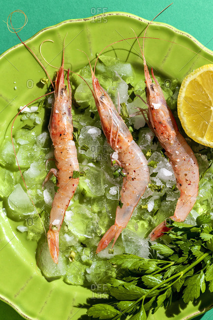 Tasty prawns placed on green plate with half of lemon and bunch of fresh parsley on multicolored background