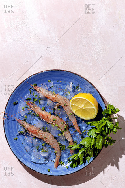 Tasty prawns placed on blue plate with half of lemon and bunch of fresh parsley on multicolored background