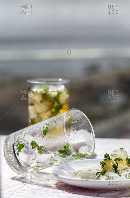 Iced tea with frozen water cubes spilled on saucer with lemon and mint