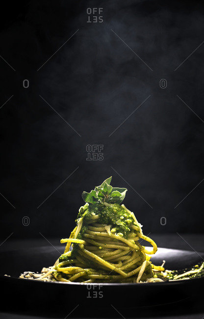 Tasty pasta with pesto sauce and Parmesan cheese served on table in black background
